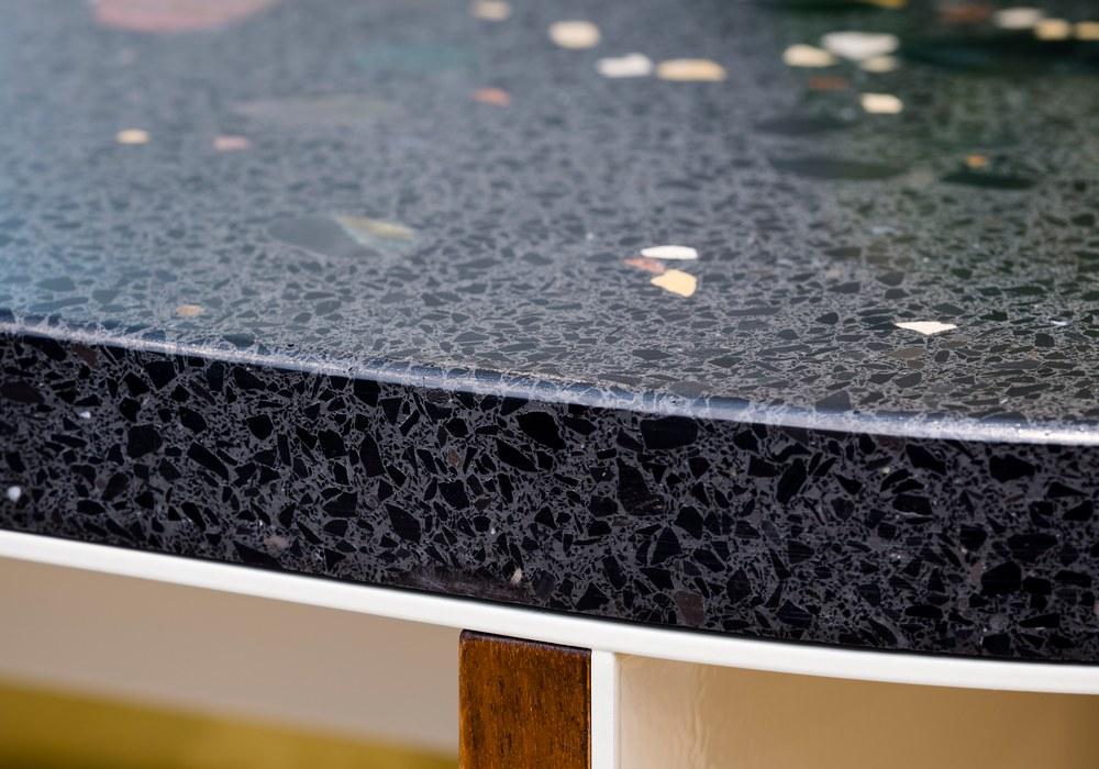 Nahaufnahme einer dunklen Tischplatte aus Terrazzo-Beton