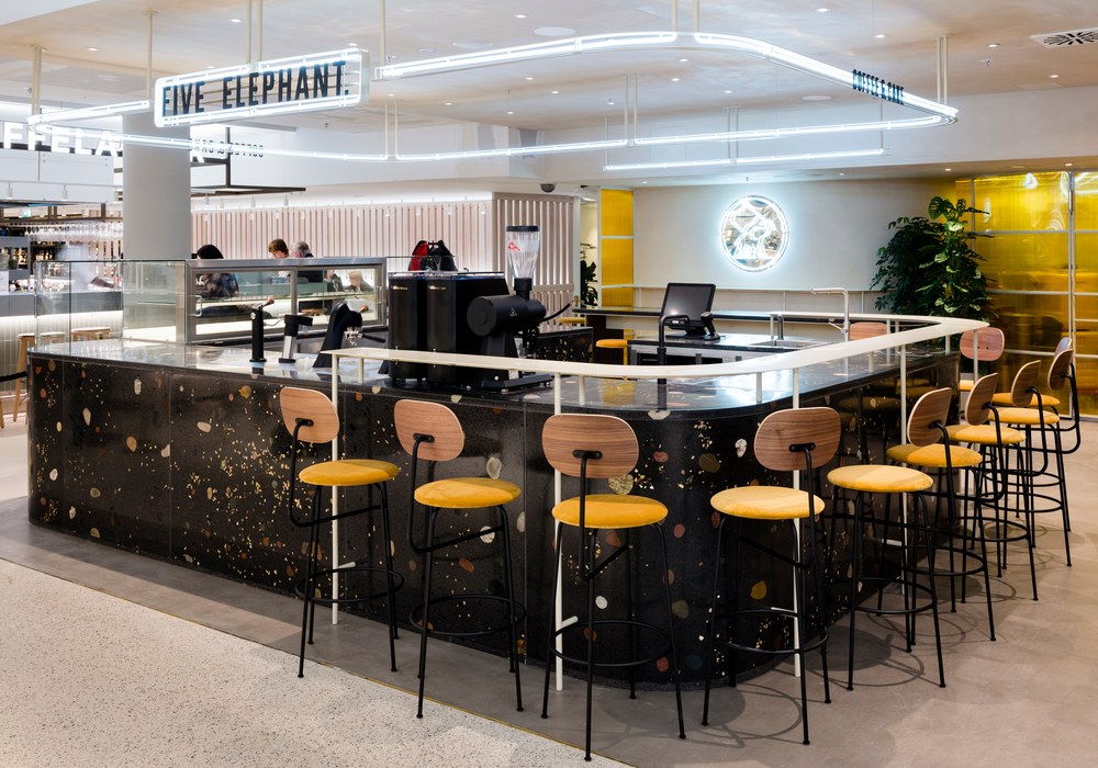 Five Elephant im KaDeWe mit Bar aus dunklem Terrazzo-Beton und orangenen Barhockern