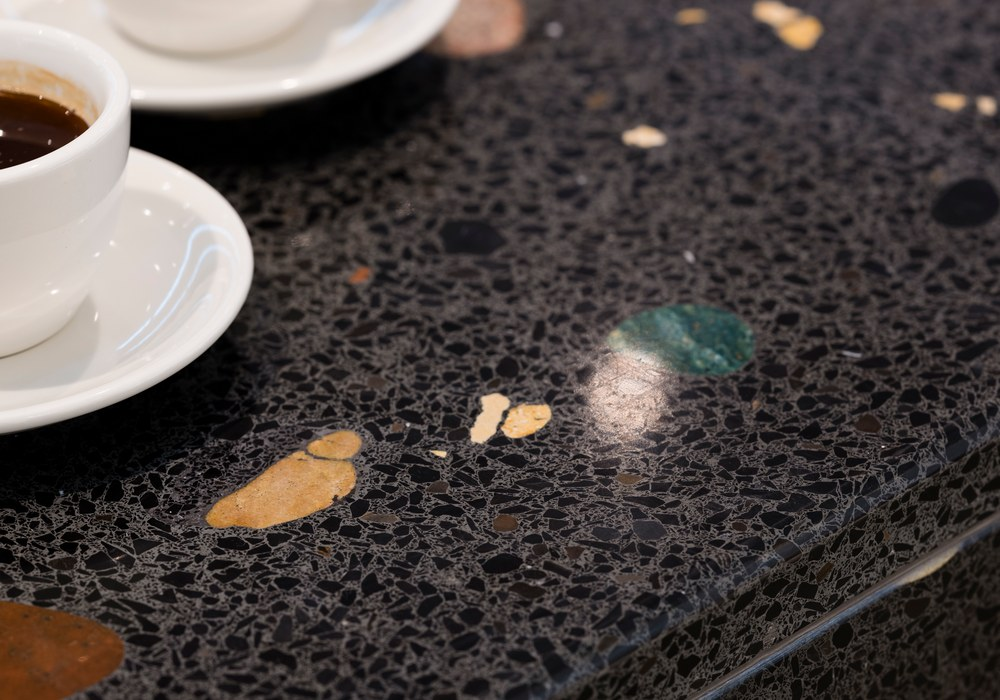 Dunkle Tresenplatte aus Terrazzo-Beton in Nahaufnahme mit Kaffeetassen